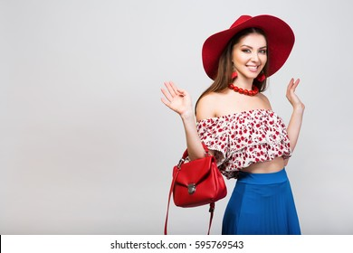 young beautiful stylish woman in trendy summer apparel, blue skirt, red hat, bag, accessories, fashion trend, sexy, smiling, happy, studio white background, resort vacation style,