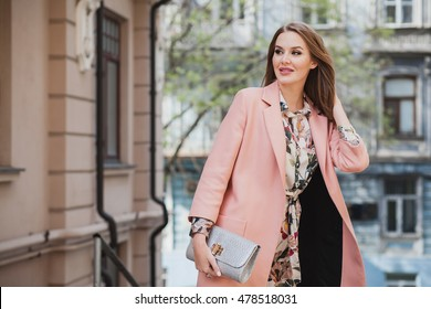 young beautiful stylish woman walking in street in pink coat, floral printed dress, holding silver purse in hands, autumn fashion trend, smiling, happy