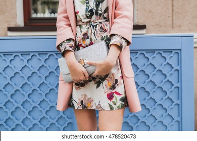 young beautiful stylish woman walking in street in pink coat, floral printed dress, holding silver purse in hands, autumn fashion trend, hands close-up, details