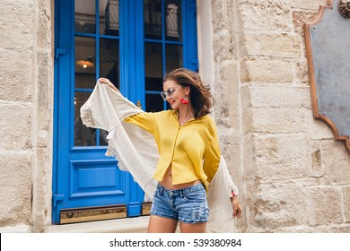 young beautiful stylish woman walking in old city street, europe vacation, bohemian outfit, freedom, happy, smiling, having fun, sunglasses