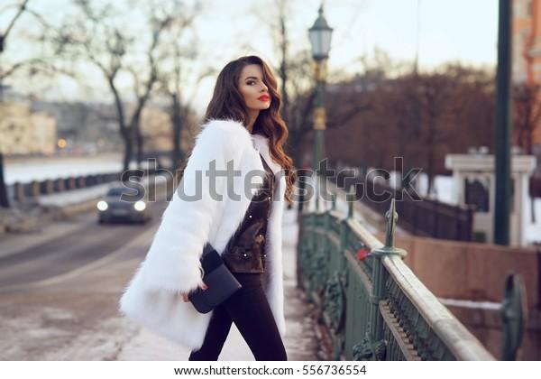 寒い冬の雪の日に通りを歩く若い美しいおしゃれな女性。黒いブラウスとズボンと白い毛皮のコートを着たおしゃれな女の子。長い巻き毛の女性。