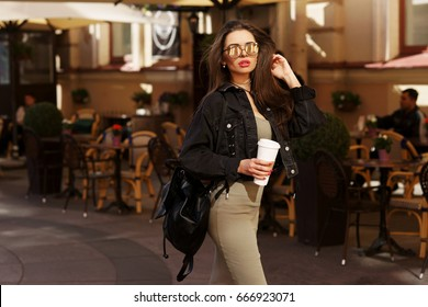 Young beautiful stylish woman wearing green dress, black jeans jacket and sunglasses walking at the street in city. Pretty brunette girl with long hair holding backpack and coffee