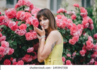 Young beautiful stylish woman in yellow jumpsuit with tattoo on her hand posing near roses flowers in a garden.