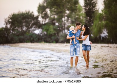 Young beautiful and stylishly dressed family of three people mom, father and daughter of one year on the shoulders of a man walking along the seashore barefoot holding his hand. The concept of a famil