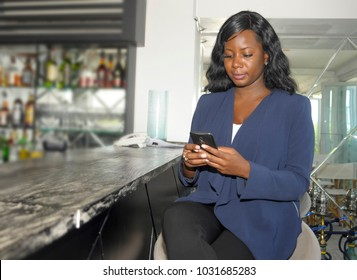 young beautiful and successful black Afro American woman on her 30s wearing formal business clothes sitting at resort restaurant bar working with mobile phone confident and happy