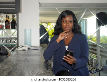young beautiful and successful black Afro American woman on her 30s wearing formal business clothes sitting at resort restaurant bar thinking about work project holding  mobile phone