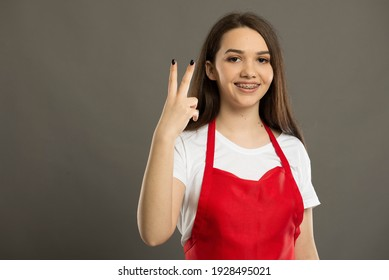 Young and beautiful supermarket employee counting to two wearing a red apron