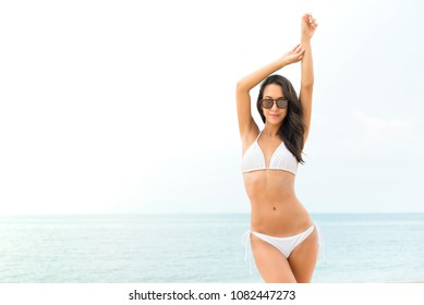 Young beautiful tan skin Asian woman in white biniki swimsuit posing at the beach in summer