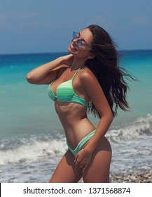 Young beautiful tanned bikini model with long dark hair in green swmsuit and sunglasses posing at pebble beach against blue sea water
