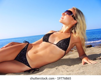 Young beautiful tanned blond woman laying on sea beach