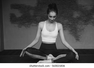 Young beautiful tanned woman practicing yoga and relaxing in lotus position on yoga mat in loft interior.