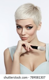 Young beautiful tanned woman with stylish cat eye make-up and platinum blonde hair holding makeup brush