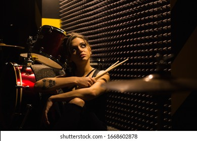 young beautiful tattooed girl in a leather jacket plays drums in a recording Studio on the bright black and yellow band.