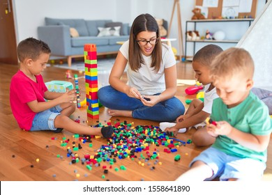 Young beautiful teacher and toddlers playing with building blocks around lots of toys at kindergarten