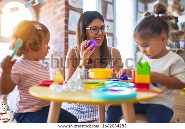 Jeune professeur et tout-petit jouant aux repas avec de la nourriture en plastique et des couverts à la maternelle