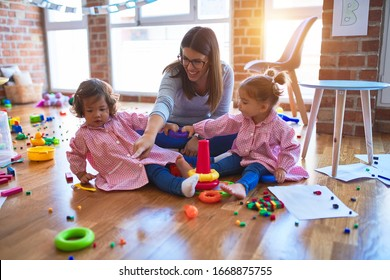 Young beautiful teacher and toddlers wearing uniform building pyramid using hoops at kindergarten