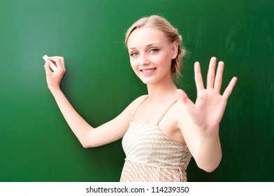young beautiful teacher writes on the blackboard with chalk and shows five points