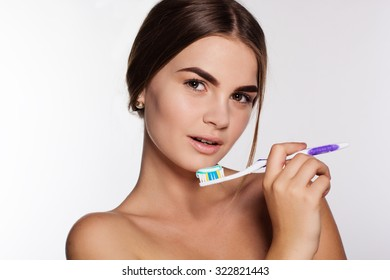 Young beautiful teen girl is holding toothbrush with toothpaste isolated on white background