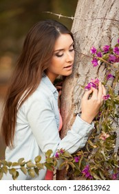 young beautiful teen woman smells flowers