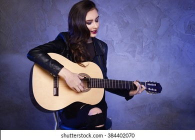 Young beautiful teenage girl playing on guitar. Concert. Hobby. Rock and roll.