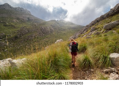 Young, beautiful, teenage woman with backpack hiking in mountains. Serra de Tramuntana, Mallorca, Spain
