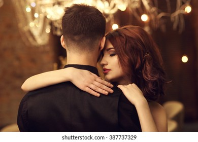 Young beautiful tender woman with red hear hugging her man. Closeup emotional portrait in evening interior with artificial lighting