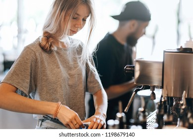 Young beautiful thin blonde with long hair,dressed in casual outfit,is opening milk next to coffee machine in a cozy coffee shop.