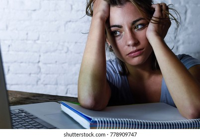 young beautiful and tired student woman working on laptop computer with notepad feeling frustrated and exhausted studying for exam late night at home in education and exam stress concept