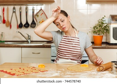 The young beautiful tired woman 30-35 years in apron sitting at a table with dough and rolling pin and going to prepare a Christmas ginger cakes in the light kitchen. Cooking home. Prepare food.