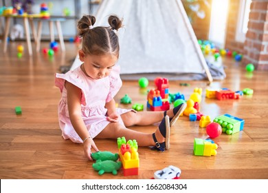Young beautiful toddler sitting on the floor playing with building blocks at kindergaten