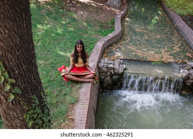 Young beautiful traditional indian woman practicing yoga in a peaceful nature environment, siddhasana pose