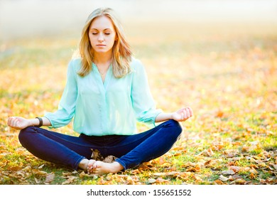 Young beautiful tranquil girl in yoga position with eyes closed on autumn background