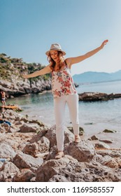 Young beautiful travel girl with hat by the seaside, trying to get balance, crystal clear blue water beach