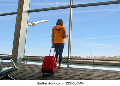 A young beautiful traveler woman see the airplane at the airport window, girl tourist with smartphone hold red bag and waiting in hall airplane departure. Travel, vacations and tourism concept