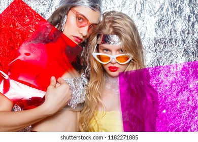 Young beautiful two girls friends on silver background. Styled Artistic Woman with Art Fancy Make-up. Vogue Style. Creativity. Fashion Girl. Beauty Portrait Woman. Beauty face with color filters