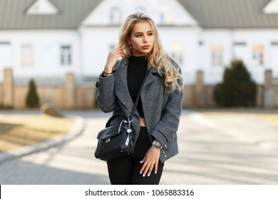 Young beautiful vogue model girl with a stylish handbag in a fashion coat on a sunny spring day