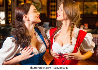 Young beautiful waitresses at the Oktoberfest party adjust their breasts in a bra.