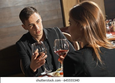 Young beautiful wealthy couple drink wine in bar.