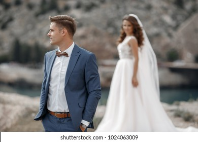 young beautiful wedding couple by sea. bride and groom hugging and kissing outdoors in summer