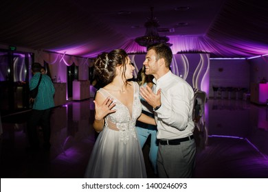 young beautiful wedding couple dancing in a restaurant and having fun bride in beautiful dress groom stylishly dressed