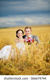 young beautiful wedding couple hugging in a field