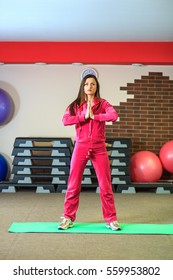 Young beautiful white girl in a pink sports suit does physical exercises at the fitness center. Hall fitness club for background. Interior of fitness club.