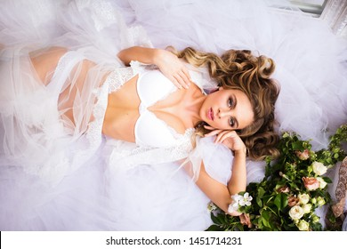 Young beautiful white-skinned Bride with gentle curls in lingerie and boudoir dress posing lying
