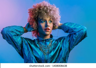 Young beautiful woman with afro style blonde hair and colorful background, wearing gold chain and blue windbreaker