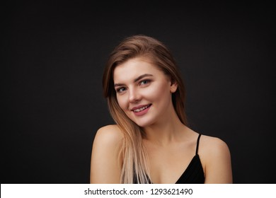 Young beautiful woman against dark background. Natural beauty