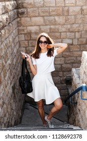 Young beautiful woman against a stone wall on camera