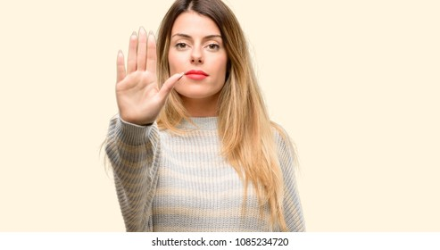 Young beautiful woman annoyed with bad attitude making stop sign with hand, saying no, expressing security, defense or restriction, maybe pushing