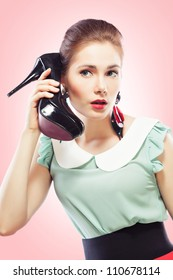 Young beautiful woman answering a shoe telephone holding it near her face and talking, pink background. Pin-up style.