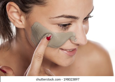 young beautiful woman applied a mask on her face