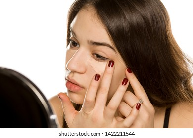 Young beautiful woman applying concealer with the fingers on white background